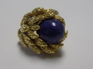 Lady's 18 Karat Yellow Gold Textured Leaf Design Ring Holding an Oval Cabochon Cut Blue Lapis Lazuli. The Ring includes a Broken Yellow Gold HorseShoe Sizer and Weighs 11.0 Grams