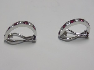 "Pair of 18 Karat White Bold ""J"" Hoop Clip-on Earrings holding Five Round Rubies Alternating and Four Round Diamonds in each. The Diamonds Weigh an Estimated 3/4 Carat Together and are (VSI) Clarity and (G) Color; the Earrings Weigh 3.9 Grams and are in Ex"