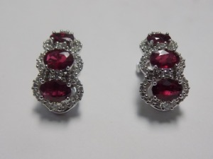 "Pair of 18 Karat White Gold ""J"" Hoop Clip-on Earrings which each hold Three Oval Rubies surrounded by Round Diamonds Weighing an Estimated 3/4 Carat Together which are (SlI-S12) Clarity and (H-I) Color. The Earrings Weigh 5.2 Grams and are in Excellent Co"