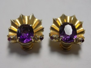 Pair of 14 Karat Yellow Gold Ribbed Clip-on Earrings Featuring an Oval Amethyst and Two Small Rubies in Each; the Earrings are in Excellent Condition and Weigh 7.8 Grams.
